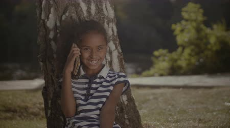 osm : Portrait of joyful curly elementary age african american girl talking on cellphone while sitting under the tree in summer park. Smiling child chatting on smart phone while resting in nature.