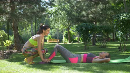 warming up : Charming sporty woman with ponytails exercising sit-ups with assistance of female friend in summer park. Active female doing abs workout with female friend holding her legs during training in nature.
