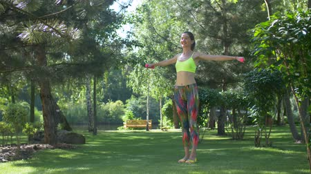 weightlifting : Smiling active woman exercising and weightlifting using dumbbells while standing on green park lawn on summer sunny day. Sporty fit female working out with dumbbells in nature. Slow motion. Stock Footage