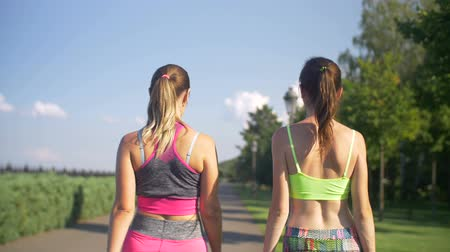 otuzlu yıllar : Portrait of smiling sporty fitness women turning back over shoulders and smiling while walking along summer park after successful workout. Fit female friends walking outdoors after training session.