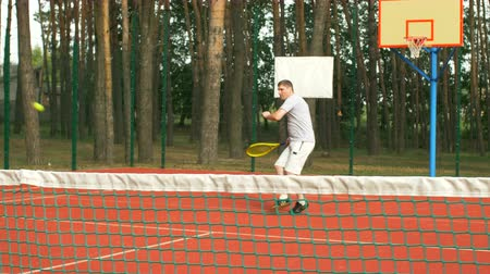 хит : Active healhty lifstyle millennial man in sports clothing playing tennis game on hardcourt. Positive amateur tennis player hitting ball with different grip techniques during training session outdoors.
