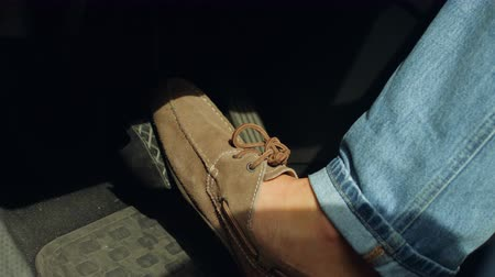 önlemek : Close-up of male driver foot in shoes pressing brake pedal while driving car on road. Man foot pressing car brake pedal to avoid car accident during a drive. Stok Video