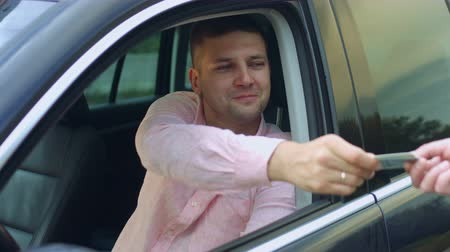 registrar : Surprised man giving driving license to police officer while sitting in his car. Handsome male driver stopped for policemans control on road and showing documents for checking to police officer. Stock Footage