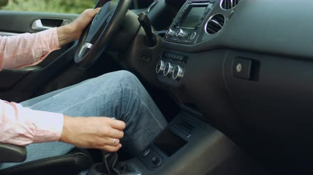 switching : Closeup of male hand on transmission stick shifting to drive mode. Man in jeans and shirt changing the car gear before driving. Driver shifting manual six gear car transmission shifter. Stock Footage