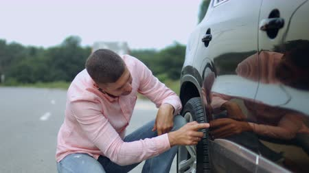 scrape : Annoyed handsome male driver with handsfree checking his car for scratches and dents outdoors. Frustrated man in casual clothes looking at scratches and dents on his new car on parking lot.