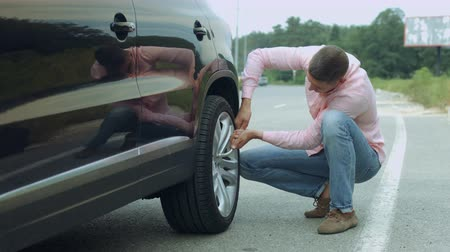 replace : Handsome driver unscrewing car wheel by pneumatic wrench on roadside to replace flat tyre on roadside. Man in casual clothes fitting car wheel with wrench after changing flat tire during road trip.
