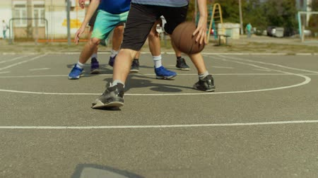 streetball : Teenage streetballer dribbling and practicing ball handling skill on basketball court during half-court play outdoors. Male basketball player dribbling and bouncing the ball low to the ground. Stock Footage