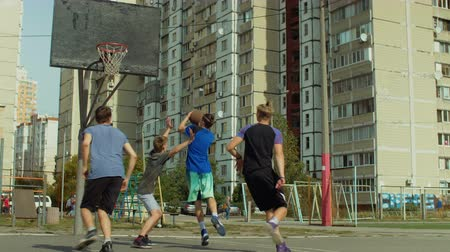 streetball : Active sporty young basketball players playing half-court game on street court. Teenage streetballer scoring a point after layup shot during basketball game over urbanscape background. Stock Footage