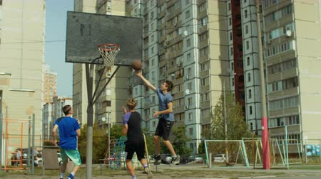 útočný : Teenage sporty streetball player scoring a point with layup shot after fast break 2-on-1 on basketball court outdoors. Young basketball player pushing the ball up court on fast break during game.