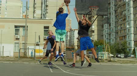 útočný : Rear view of teenage sporty streetball player taking jump shot with the resistance of defender and scoring points during basketball game while playing with friends on court outdoors. Slow motion.