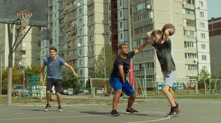 avoiding : Teenage streetball defensive player legally deflects a field goal attempt from offensive player to prevent a score while playing together with friends on basketball court over urbanscape background. Stock Footage