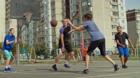 sertés : Teenage sporty streetball team making bounce passes to teammate to score field goal during basketball game on street court. Young basketball player making an successful assist to teammate outdoors.
