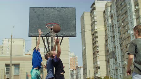 отскок : Teenage sporty streetball players jumping to take offensive rebound on basketball court during match. Three basketball players fighting for rebound after a missed field goal during basketball game. Стоковые видеозаписи