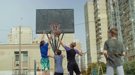 отскок : Active sporty streetball players fighting for rebound after missed shot while playing basketball game on street court. Teenage friends playing streetball outdoors and jumping to take rebound. Slo mo. Стоковые видеозаписи