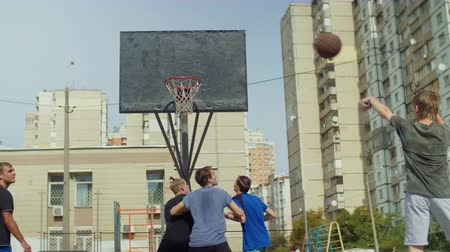отскок : Teen streetball player missing a shot after assit and players fighting for rebound while playing basketball game on outdoor court. Active sporty teenagers playing streetball match on basketball court.