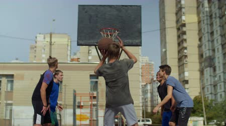 basketball : Rear view of sporty teenager basketball player taking a free throw and scoring point while playing streetball game on basketball court on street. Streetball man shooting a free throw after foul.