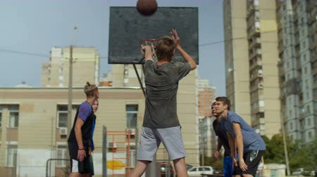 basketball : Rear view of active sporty teenager taking a free throw and missing a point while playing streetball game on basketball court outdoors. Basketball player shooting free throw and failed to score point.