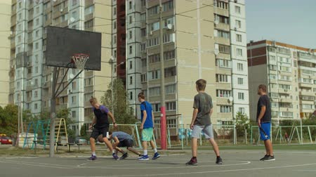 útočný : Sporty teenager defensive player committing a foul against opponent during playing streetball game on basketball court on street. Basketball player making illegal contact against opposing player.