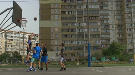 hoop : Sporty teenage basketball players playing streetball game on basketball court over cityscape background. Side view. Streetball player failing to score field goal after assist during basketball game.