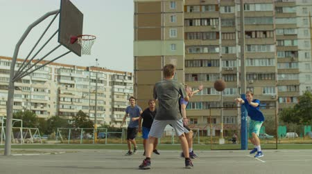 five : Offensive streetball team making chest pass and scoring field goal while playing basketball game on outdoor court. Teenage streeball players passing the ball and scoring points during basketball match