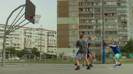 útočný : Teenage basketball team passing ball on court and scoring field goals with layup shot while playing streetball game on street. Streetball player making successful assist to his teammate during match.