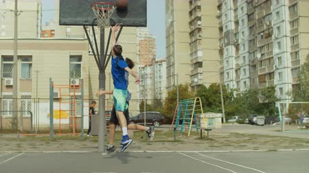 defending : Teenage streetball players playing one on one game on basketball court on street. Baskeball player dribbling and scoring points after layup shot while playing streetball together with friend outdoors.
