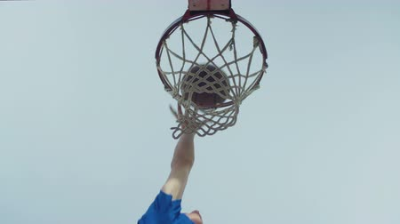 basketbalveld : Basketbal die door openluchtbasketbalhoepel gaan over blauwe hemelachtergrond. Basketbal lay-up shot, scoorde de winnende punten op streetball game scene van net onder het net. Slow motion. Stockvideo