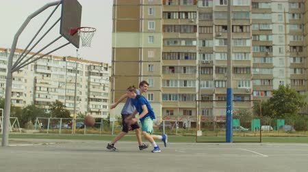 defending : Teenage streetball player dribbling and taking field goal shot while playing basketball game together with friend on street court. Basketball players playing one on one streetball game outdoors.