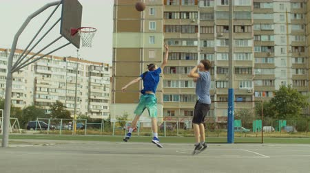 avoiding : Handsome streetball player scoring points after jump shot on basketball court while playing one on one game on street. Basketball player taking jump shot and opponent trying to block shot outdoors.