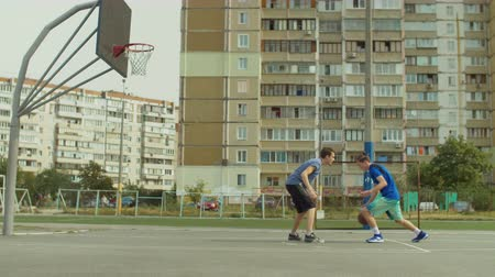 útočný : Handsome teenage streetball player dribbling and scoring points in the paint after jump shot on basketball court while playing one on one game. Teenage basketball player scoring field goal outdoors.
