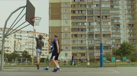 útočný : Active teenage friends playing two on two streetball game on outdoor basketball court. Young basketball player scoring field goal with layup shot after assist from his teammate during game outdoors. Dostupné videozáznamy