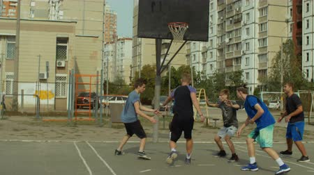 útočný : Offensive streetball player scoring field goal with layup shot after pocket pass from teammate while playing game on street bsketball court. Basketball team completing their attack and scoring points