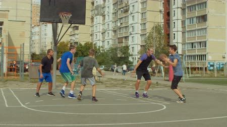 útočný : Teenage sporty basketball player dribbling and passing the ball to his teammate while playing streetball on court. Streetball player scoring points in the paint with layup shot during basketball game. Dostupné videozáznamy