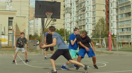 obránce : Teenage basketball forward setting a screen on defender and receiving a pass from teammate, taking easy layup shot during streetball game. Streetball team making successful pick and roll play on court
