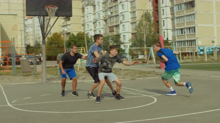 útočný : Teenage sporty friends practicing streetball game on outdoor court. Streetball player setting a screen on defender and taking easy jump shot while playing game on basketball court on street. Slo mo.