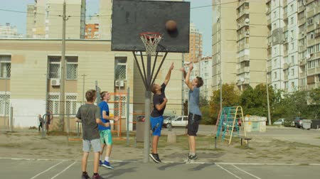 defending : Offensive streetball team scoring field goal in the paint while playing basketball game on outdoor court. Baskteball player making successful assit to his teammate during streetball match ooutdoors.