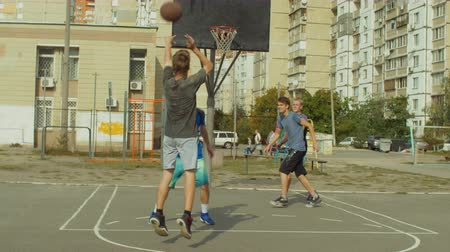 útočný : Teenage friends having fun and playing streetball game on outdoor basketball court. Young basketball player scoring field goal after a set shot while playing streetball match outdoors. Slow motion. Dostupné videozáznamy