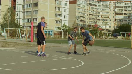 sertés : Offensive streetball player dribbling and bouncing the ball while playing basketball game on court over urbanscape background. Friends practicing and training streetball on basketball court outdoors.