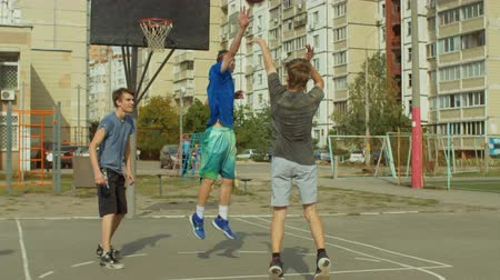avoiding : Sporty streetball player bouncing ball and taking jump shot to score field goal while playing game on outdoor basketball court. Offensive player scoring points, avoiding blockshot of defender outdoors Stock Footage