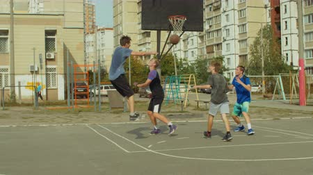 sertés : Offensive streetball team scoring field goal with layup shot while playing two on two game on basketball court on street. Basketball player scoring point after successful assist from teammate outdoors Stock mozgókép