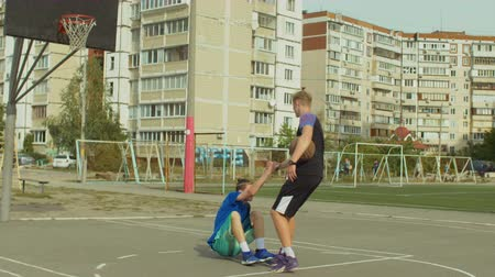 streetball : Streetball player with ball helping fallen opponent to get up from basketball court after committed foul while playing one on one streetball game. Man extending hand to lift opponent fallen on ground.