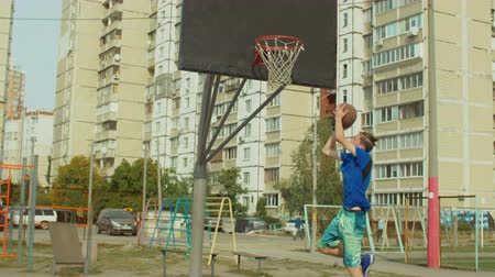 streetball : Rear view of teenage basketball player dribbling and practicing ball handling skills on outdoor court over cityscape background. Young streetball player bouncing the ball and taking a shot outdoors. Stock Footage