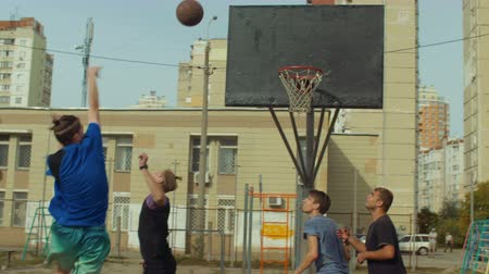 obránce : Handsome teenage basketball player completing offense with jump shot and scoring points while playing streetball game on outdoor court. Young streetball player taking jump shot to score points outdoor