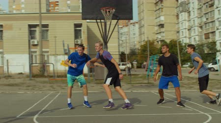 skorlama : Active sporty teenage friends spending great time playing basketball on outdoor court. Healthy lifestyle young men practicing streetball game on basketball court. Slow motion.
