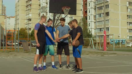 unir : Teenage basketball team stacking hands on court before starting playing streetball game. Team of streetball playing making pile of hands, showing unity and willing to win basketball match outdoors.