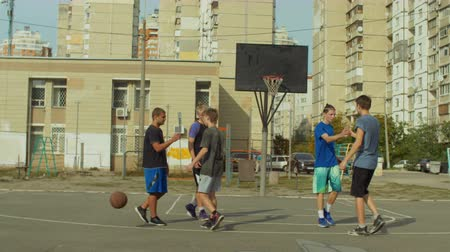 saygı : Teenage streetball players congratulating each other and shaking hands after basketball match on outdoor court. Cheerful basketball players showing respect to each other for fair competition outdoors. Stok Video