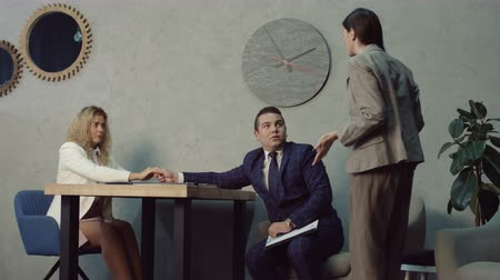 desejo : Handsome businessman flirting over desk with beautiful seductive secretary in office while waiting for appointment with executive. Business colleagues receiving rebuke from angry boss for office flirt