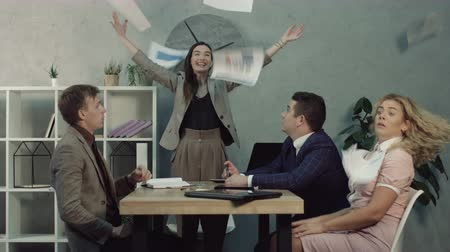 bochechudo : Excited carefree businesswoman throwing papers in the air and having fun during team meeting. Surprised business colleagues sitting in boardroom while team leader fooling around in office. Vídeos