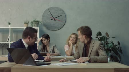 corporate affairs : Office flirt. Attractive blonde woman flirting over desk with her handsome coworker while working together in open space office. Playful female colleague ogling with male employee at workplace. Stock Footage