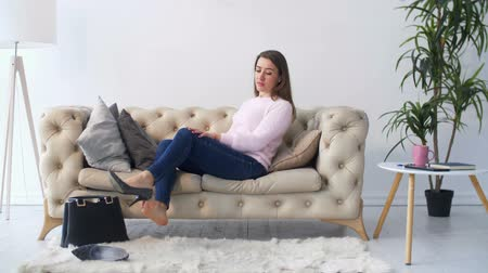 coming home : Charming woman in stylsih outfitt sitting on sofa, wiith feet taking high heels shoes off in domestic room after coming home from work. Beautiful female taking a rest on the couch after working day. Stock Footage
